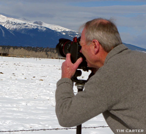 Tim Carter taking a photo of the snow capped Rocky Mountains